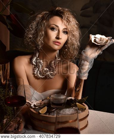 Beautiful Arrogant Blonde Curly Hair Woman In Seafood Restaurant Eating Oysters And Drink Wine Holdi