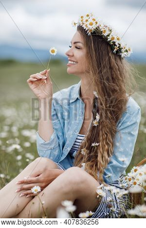 Young, Beautiful Woman In A Wreath Of Wild Flowers, Spends Time Alone Outdoors Among White Meadow Da