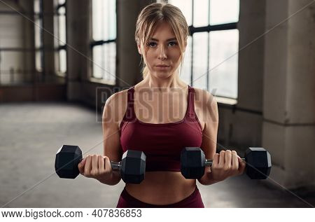 Young Strong Muscular Woman Doing Weight Exercise With Dumbbells During Intense Fitness Workout In S