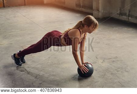 Side View Of Slim Female In Sportswear Doing Plank Exercise On Ball During Fitness Training In Gym