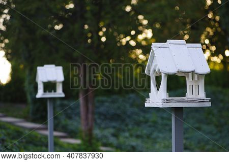 Wooden Bird Feeder With Berries And Wheat Inside, Birdhouse On A Beautiful Blurred Background Of Gre