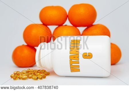 Vitamin C Bottle With Scattered Softgel And Oranges. Isolated On White Background. Healthy Immune Sy