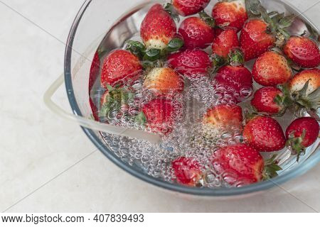 Strawberry In A Bowl With Water With A Round Ozonating Stone. Tubes Leading To Oxygen Pump And Ozone