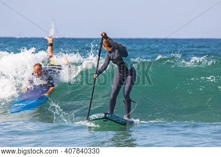 09-12-2020, Hendaya, France.young Woman With Wetsuit On An Inflatable Paddle Sup Surfboard Preparing