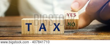 Wooden Blocks With The Words Tax, Yes Or No. Taxes Payment Concept. Tax Evasion. Taxation. Business