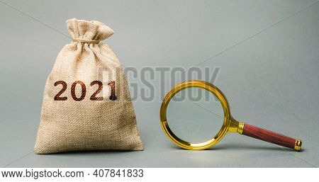 2021 Money Bag And Magnifying Glass. Budget Planning. Financial Goals And Plans. Business And Financ