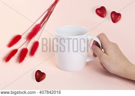 White Mug Mockup. Woman's Hand Holds Mug. Romantic Composition With White Mug, Red Fluffy Twigs And