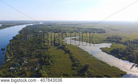 Drone Fly Over Waving River Of Blue Color Surrounded By Local Village With Various Buildings And Wet