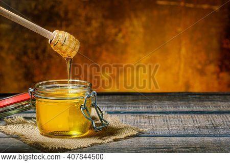 Honey Dripping From Honey Dripper Into Honey Jar
