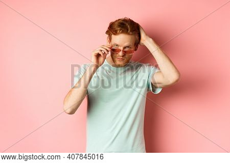 Handsome Young Redhead Man In Sunglasses, Brushing Hair With Hand And Looking Smug And Confident At