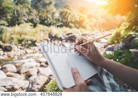 Woman Hand Writing On Notebook With Pencil At River Background.