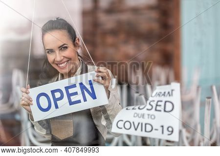 Happy Waitress Smiles Above The Open Sign As Restaurant Reopens After Corona Pandemic.