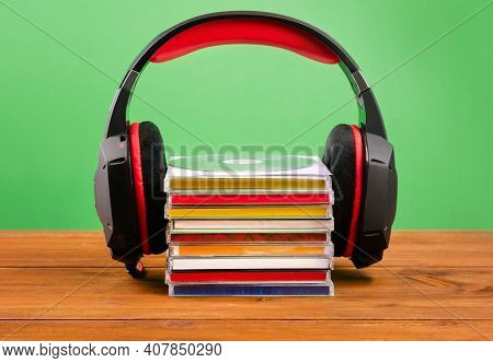 Headphones On A Stack Of Cds On A Green Background.