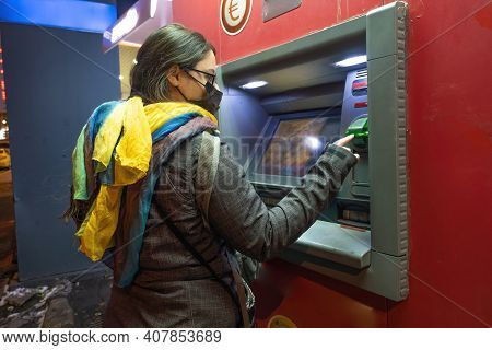 A Young Woman Withdrawing Cash In Front Of Atm In City In The Evening Time