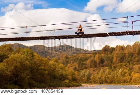 Young Woman Is Practicing Yoga On Bridge Over River High In Mountains On Background
