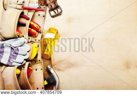 Tool Belt With Carpenter Tools And Protective Wear On Plywood Sheet Flat Lay View