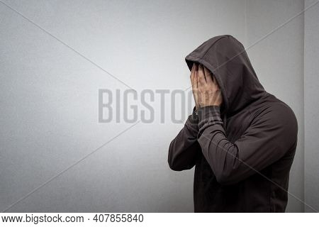 Portrait Of Young Adult Man In The Gray Hood Covered His Face With His Hands. The Concept Of Addicti