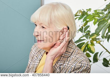 Hearing Loss Treatment Concept At Older People. Senior Woman With Hearing Aid Behind The Ear Listens