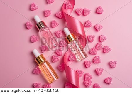 Skin Care Essence Glass Bottles On Pink Background With Heart Shape Decorations And Ribbon. Hydratin