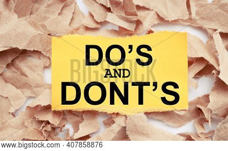 Do's And Don't's Message. Text On Yellow Paper On Torn Paper Background.