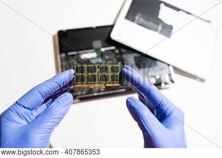 Service Engineer Installs New Ram Memory Chips To The Laptop. Repairing And Upgrading Laptop Concept
