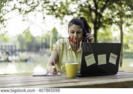 Young Woman Wearing Open Protective Face Mask Using Laptop Outdoors - Female Entrepreneur Taking Not