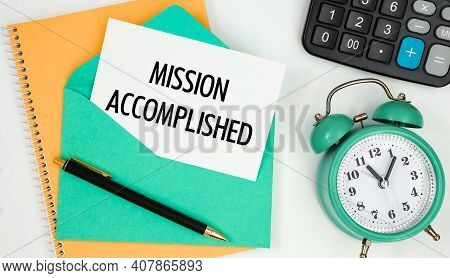 Card On A Postal Envelope With The Text Mission Accomplished, Clock, Calculator, Pen.