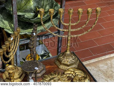 Old Bronze Menorah Candlestick Across Other Candelabras Close-up On The Antique Market. Jewish Cultu