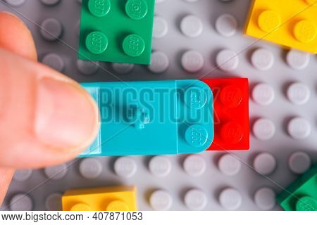 Tambov, Russian Federation - January 17, 2021 Person Hand With Lego Teal Brick Separator Removing Re