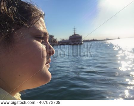 A Tween Girl Looking At Sea And Out Of Focus Ships Near The Sea In Winter Time Selective Focus