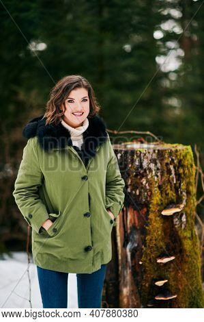 Warm Winter Portrait Of Happy Young Woman Hiking In Forest, Wearing Green Fashion Parka