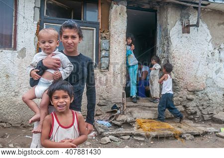 05-16-2018. Lomnicka, Slovakia. A Roma Or Gypsy Young Woman Holding A Baby In An Abandoned Community