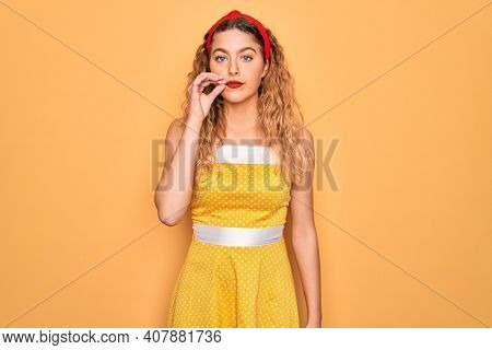 Beautiful blonde pin-up woman with blue eyes wearing diadem standing over yellow background mouth and lips shut as zip with fingers. Secret and silent, taboo talking
