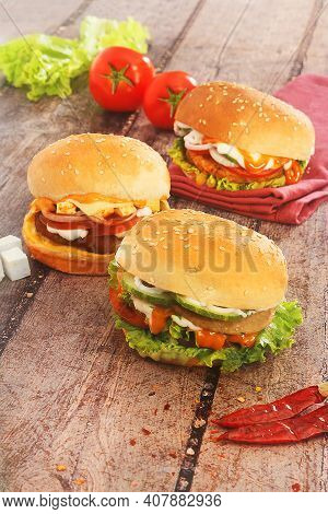 Delicious Veg And Non-veg Burgers Placed On A Wooden Board
