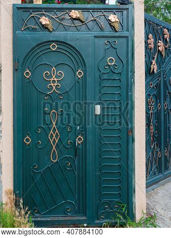 Dark Turquoise Iron Gate With A Forged Pattern In The Form Of A Golden Vine, Monograms And Gilded Tr