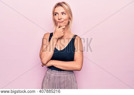 Young beautiful blonde woman wearing casual black t-shirt standing over pink background thinking concentrated about doubt with finger on chin and looking up wondering