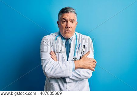 Middle age handsome grey-haired doctor man wearing coat and blue stethoscope shaking and freezing for winter cold with sad and shock expression on face