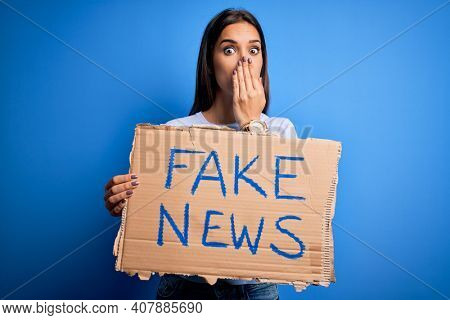 Young beautiful brunette woman holding banner with fake news message cover mouth with hand shocked with shame for mistake, expression of fear, scared in silence, secret concept
