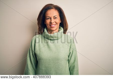 Middle age beautiful woman wearing casual turtleneck sweater over isolated white background with a happy and cool smile on face. Lucky person.