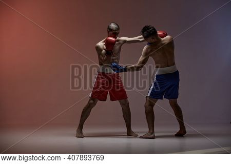 Sparring Of Athletic Guys, Boxers Fighting In Red Studio Light With Copy Space, Mixed Fight Workout