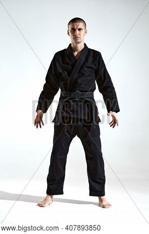 Confident Frowning Male In Black Kimono For Karate Or Kudo On White Studio Background With Copy Spac