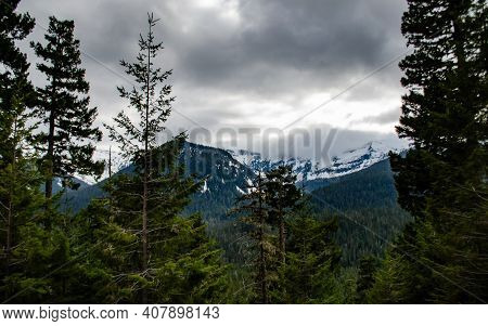 Mountains In The Snow, Overgrown With Wood. Thick Clouds Over The Mountains. Montana