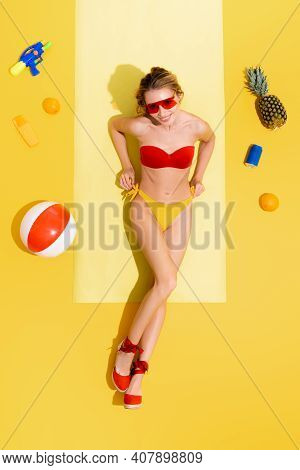 Top View Of Cheerful Woman In Swimsuit Near Water Gun, Sunscreen, Inflatable Ball, Can Of Soda And F