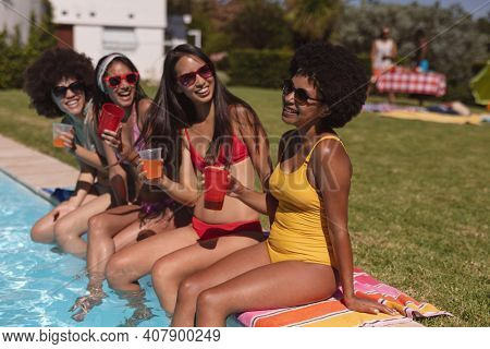 Diverse group of female friends drinking drinks sitting at the poolside. Hanging out and relaxing outdoors in summer.