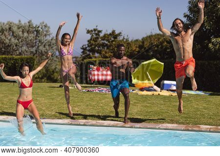 Diverse group of friends having fun and jumping into water at a pool party. Hanging out and relaxing outdoors in summer.