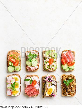 Set Of Different Sandwiches With Meat, Vegetables, Seafood. Assortment Open Sandwiches On Light Ston