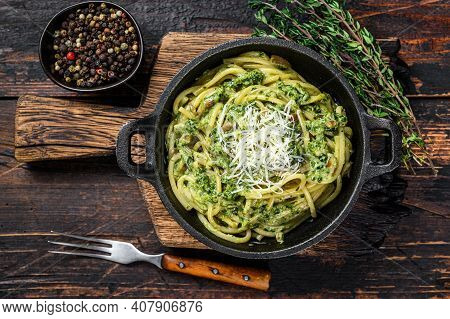 Spaghetti Pasta With Pesto Sauce, Spinach And Parmesan In A Pan. Dark Wooden Background. Top View