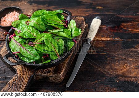 Fresh Raw Chard Leaves, Mangold, Swiss Chard In A Pan. Dark Wooden Background. Top View. Copy Space