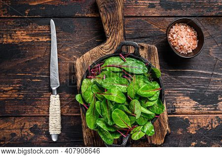 Fresh Raw Chard Leaves, Mangold, Swiss Chard In A Pan. Dark Wooden Background. Top View