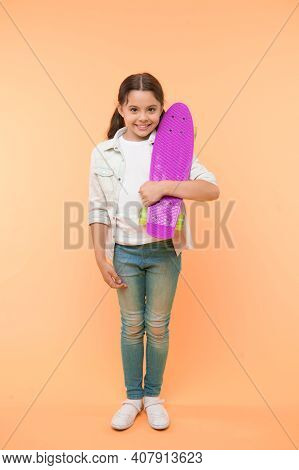 Ready To Ride. Kid Girl Happy Carries Penny Board. Child Likes Skateboarding With Penny Board. Moder